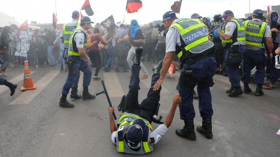 A police officer is knocked down during clashes with demonstrators protesting in front of the National Congress in Brasilia