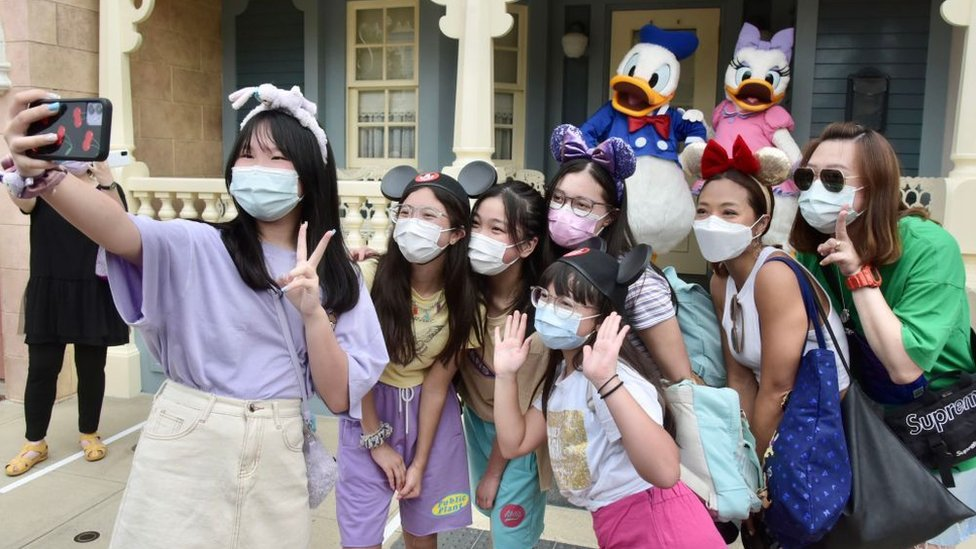 People wearing face masks visit Hong Kong Disneyland on the first day of the reopening.
