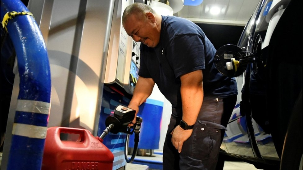 Un hombre repostando gasolina