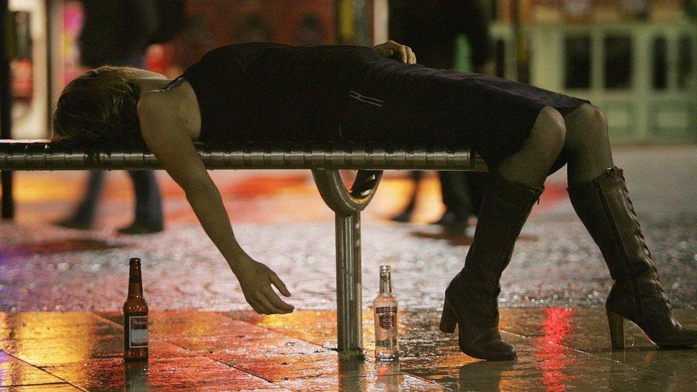 Una mujer recostada sobre un banco con botellas de cerveza en el suelo.
