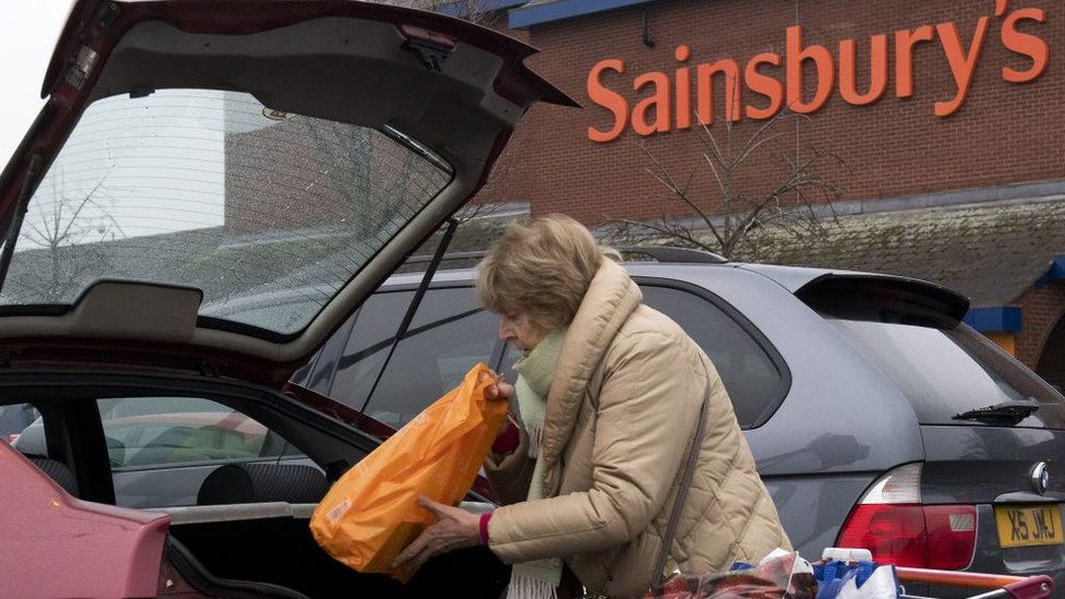 Woman loading car in Sainsbury's car park
