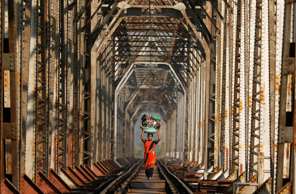 A woman carries luggage along a railway track