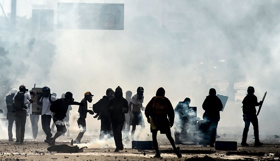Anti-government protesters and police are shrouded by teargas during a demonstration which blocked the Francisco Fajardo highway in Caracas in May 2017