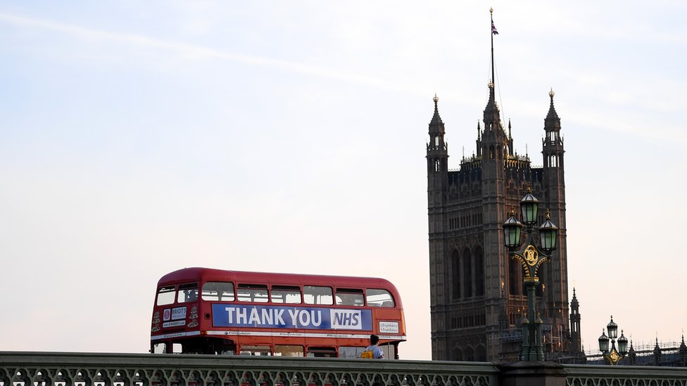 London bus drives past Big Ben