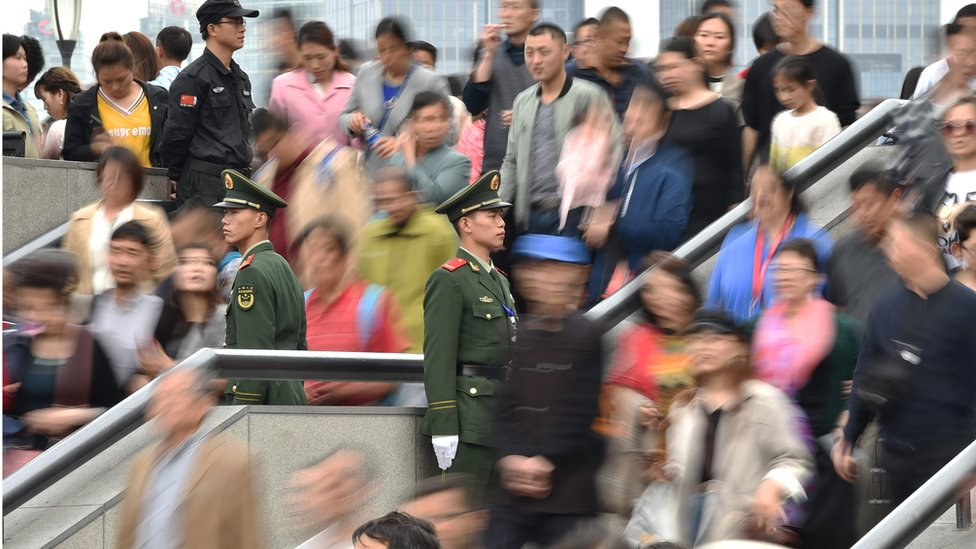 Chinese military police stand guard as people visit the promenade on the Bund