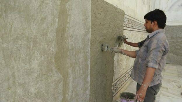 Un hombre aplicándole mascarilla de lodo al Taj Mahal