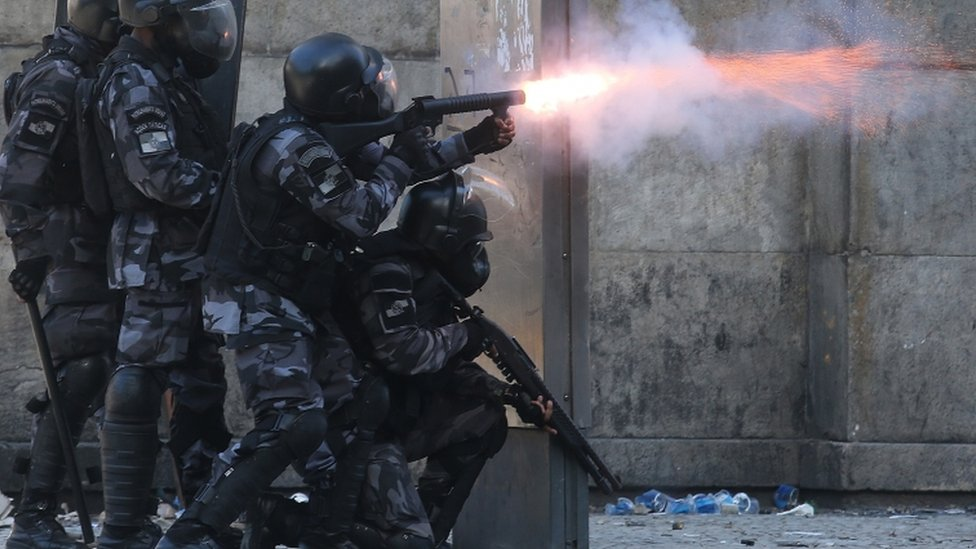 Police fire towards protesters during a protest against proposed austerity measures on 6 December 2016 in Rio de Janeiro, Brazil