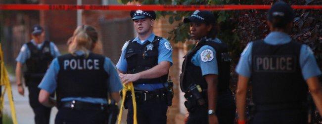 Police officers reuse crime scene tape on July 28, 2016, in Chicago.