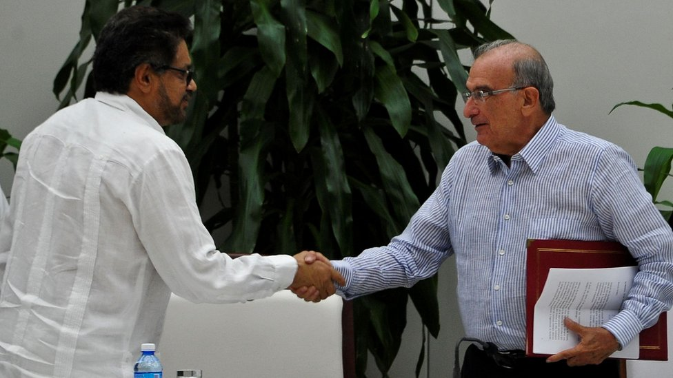 Guerrilla commander Ivan Marquez (left) and the head of the Colombian delegation for peace talks Humberto de la Calle (right) shake hands after signing a new peace agreement in Havana, 12 November 2016