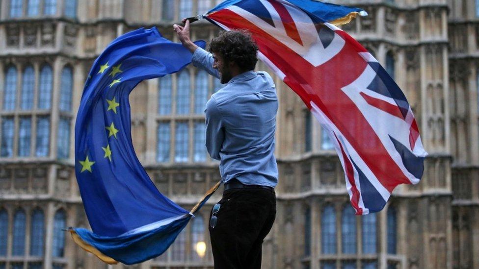 Man waving a union flag and an EU flag