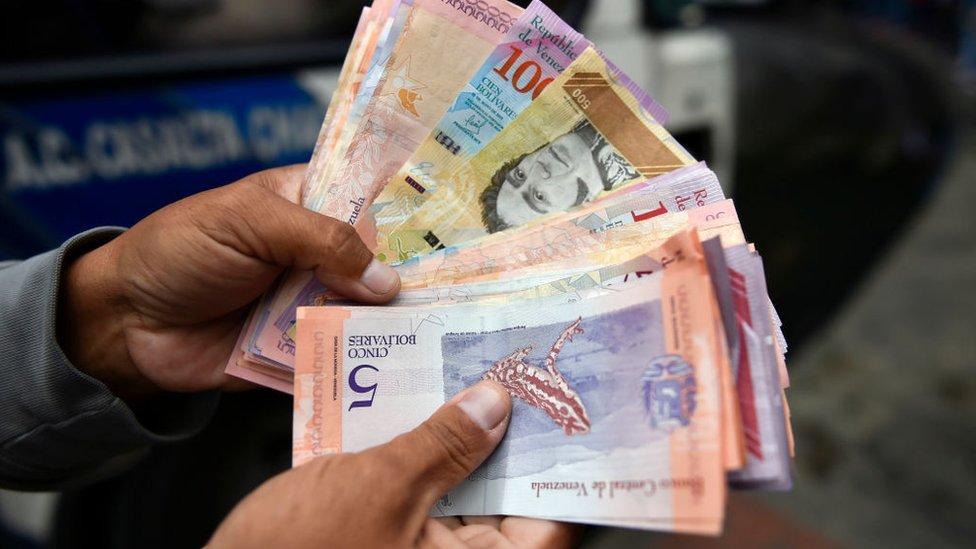 Una mano con billetes en Venezuela.