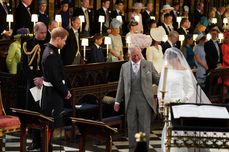 Prince Harry looks at his bride, Meghan Markle, as she arrives accompanied by the Prince of Wales