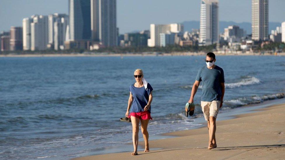 Pessoas caminham em praia de Da Nang, no Vietna