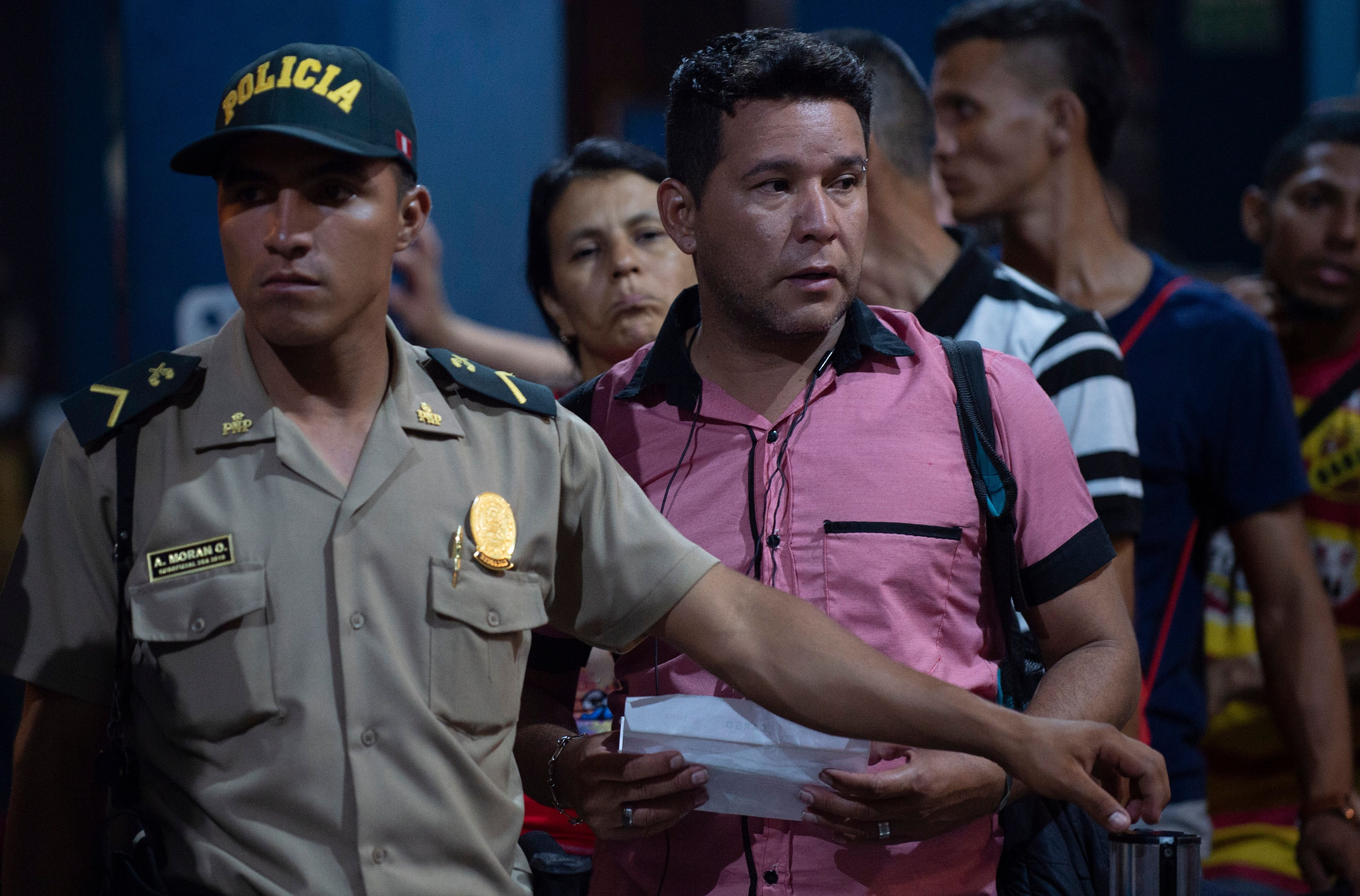 A Peruvian policeman assists Venezuelan citizens waiting in line to get a refugee application at a Peruvian border post at the binational border attention centre (CEBAF) in Tumbes on June 14, 2019.