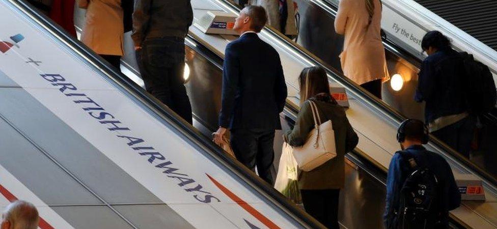 People on escalator passing BA logo