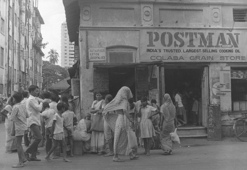 circa 1970: Customers queue outside a dry food shop in Bombay, India.