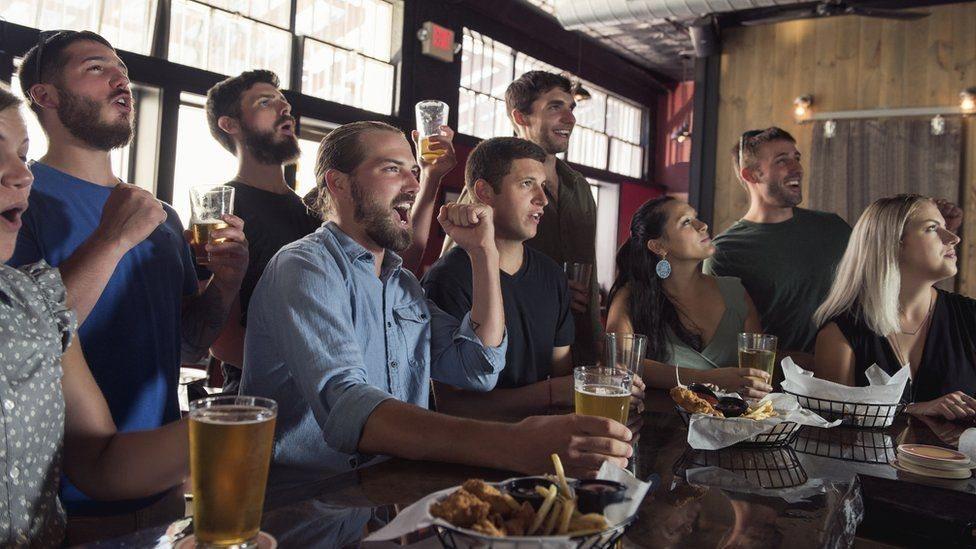 رجال ونساء يجتمعون على مائدة بينما يشاهدون شيئا