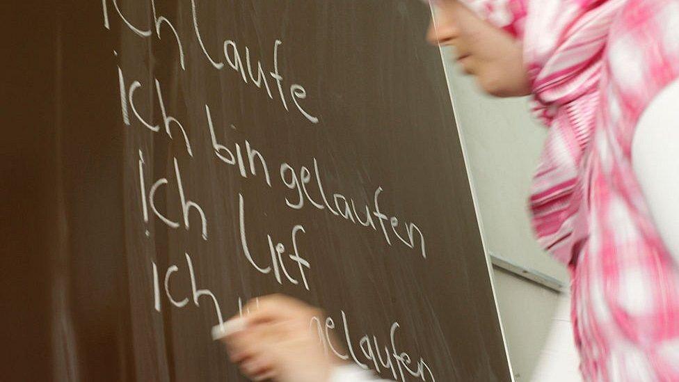 فتاة ترتدي الحجاب وتكتب باللغة الألمانية على اللوح