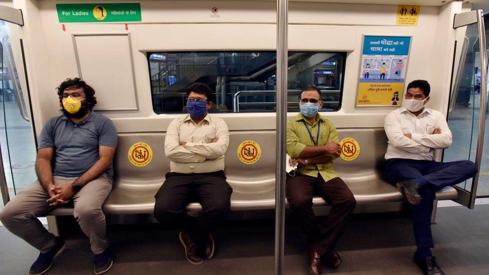 Personas en el metro con mascarilla