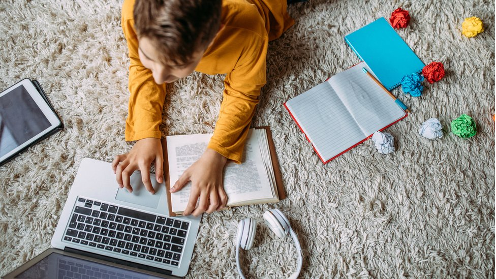 Teenager with laptop book and tablet