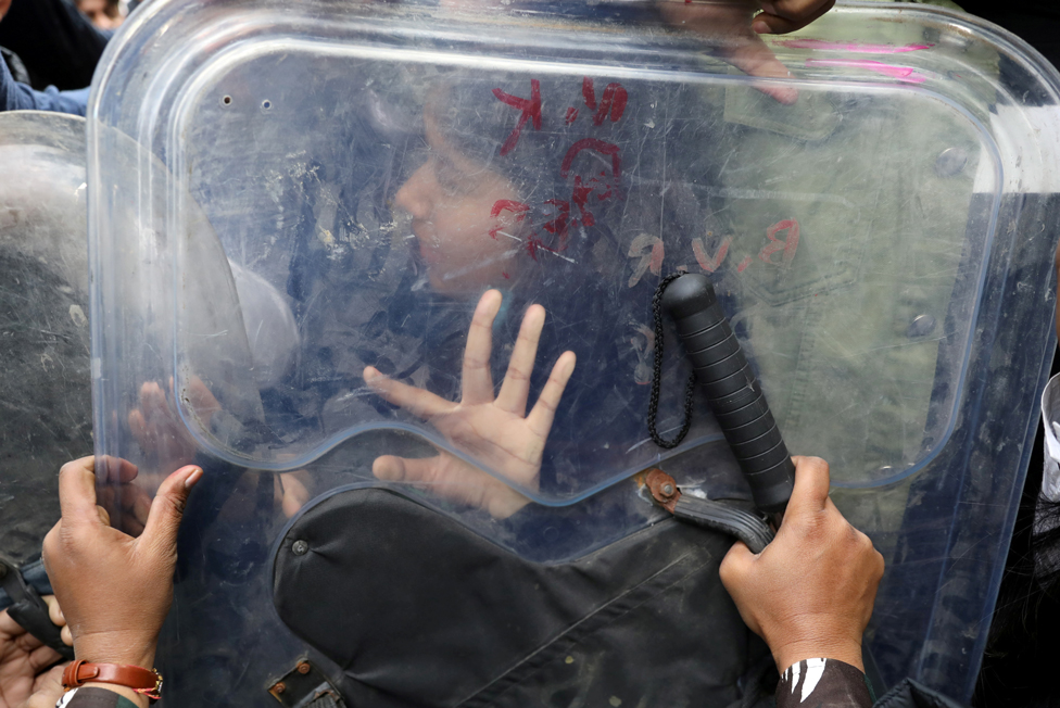 امرأة تصد بيدها درع شرطي