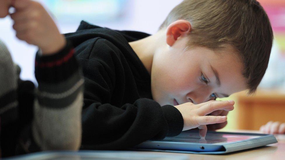 A boy looks at a tablet