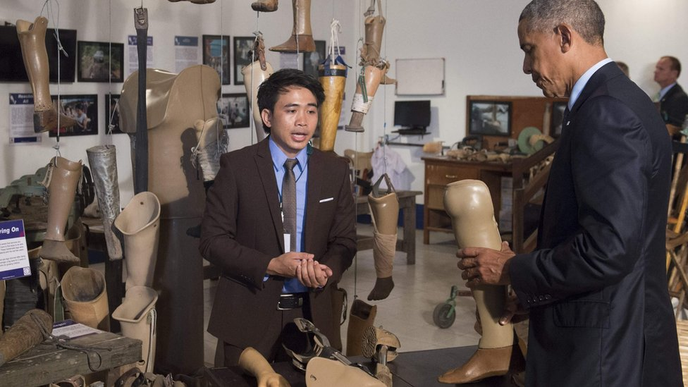 US President Barack Obama holds a prosthetic limb as he tours the Cooperative Orthotic and Prothetic Enterprise (COPE) visitor center in Vientiane on September 7, 2016