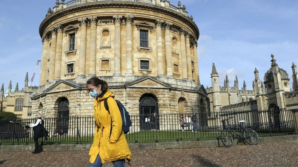 Woman wears mask walking past Radcliffe Camera