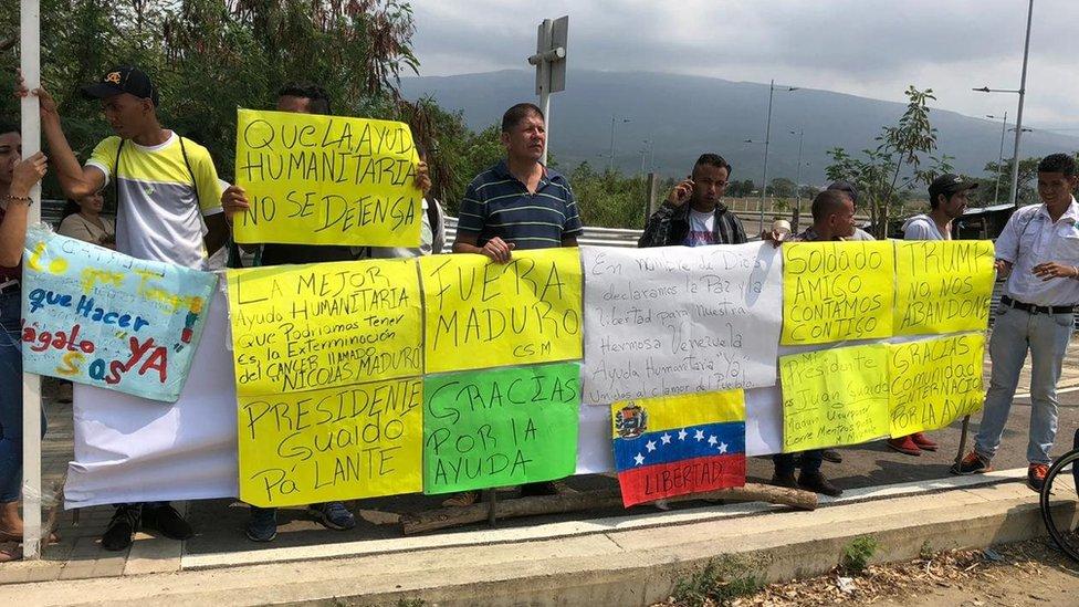 Personas apoyando la llegada de ayuda de EEUU.