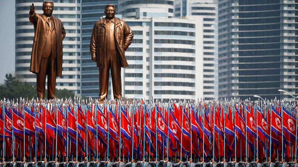 soldados frente a estatuas de los líderes