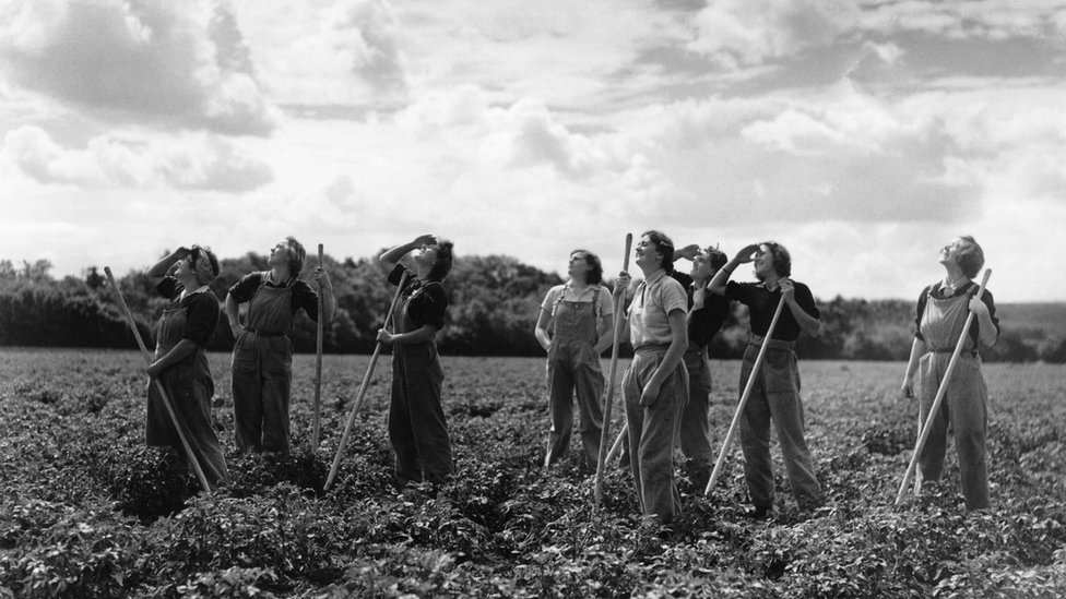 Women looking out for airplanes while working in a field during the second World War