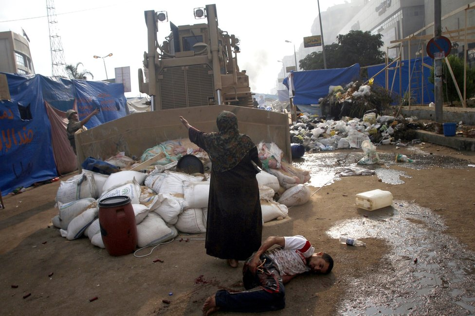 An Egyptian woman tries to stop a military bulldozer from hurting a wounded youth during clashes in Rabaa al-Adawiya square in Cairo on 14 August 2013