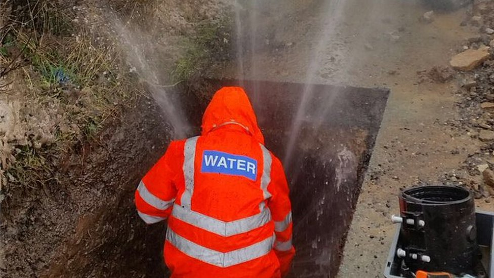 A Severn Trent engineer fixing a burst pipe as water sprays into the air