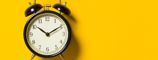 An alarm clock pictured on a yellow background