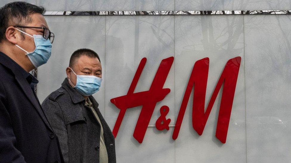 Dos hombre caminan frente a un logo en H&M en Shangái.