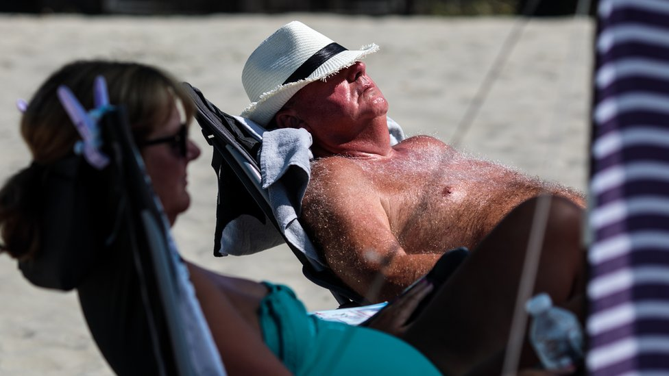 A man lies in the sun on British beach with midriff exposed to sun