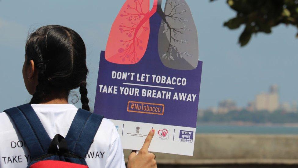 """Una joven de espaldas sostiene un cartel: """"No dejes que el tabaco te quite la respiración""""."""