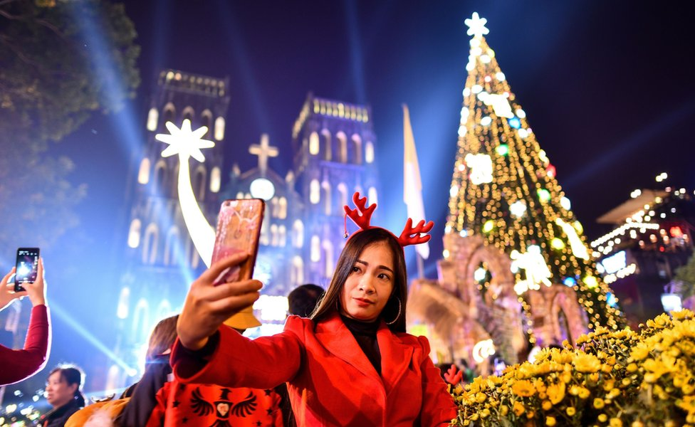 "A woman takes a selfie outside . Joseph""s cathedral in Hanoi on December 24, 2019."