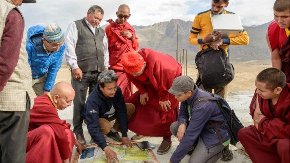 Group of people including Sonam Wangchuk gathering around ice stupa plans