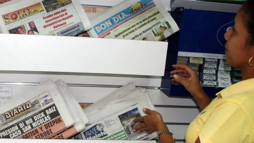 A woman looks headlines in the Aruba press