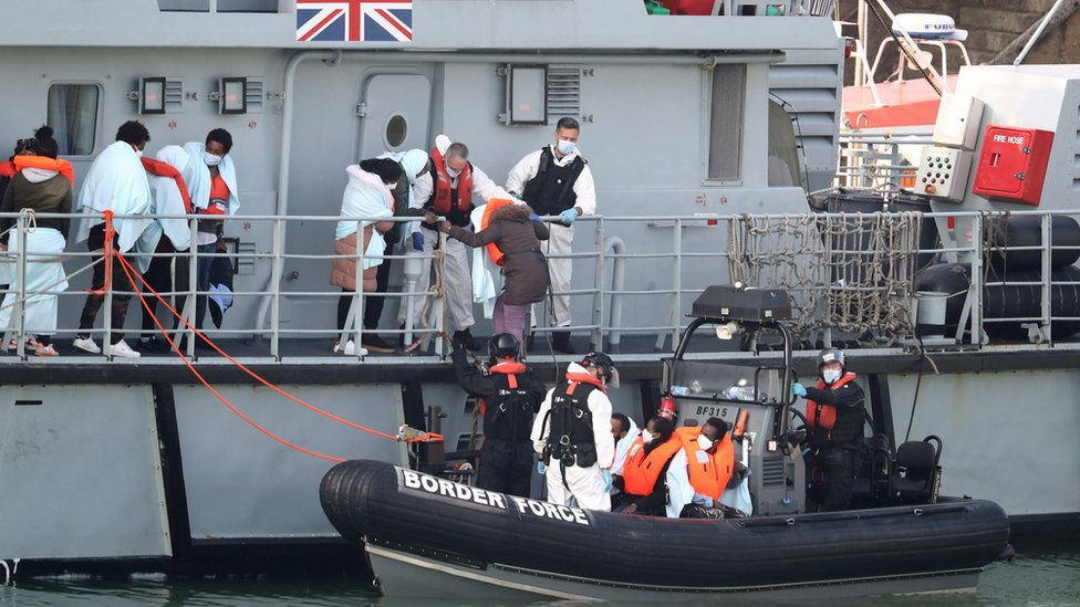 A group of people, thought to be migrants, disembark the deck of HMC Seeker, as they climb aboard a Border Force rib at Dover marina