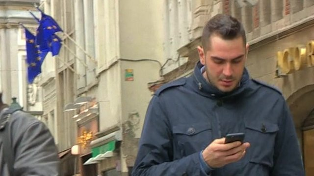 Man walking looking at mobile phone, EU flags in background