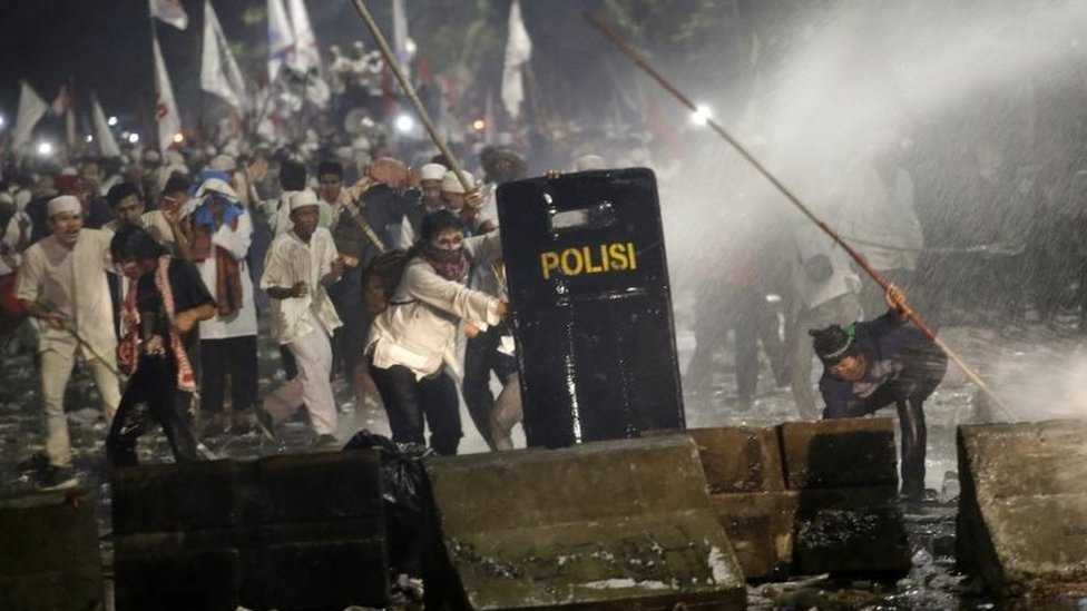 Protesters are sprayed with water from a police water cannon truck during a clash outside the presidential palace in Jakarta, Indonesia, Friday, Nov. 4, 2016