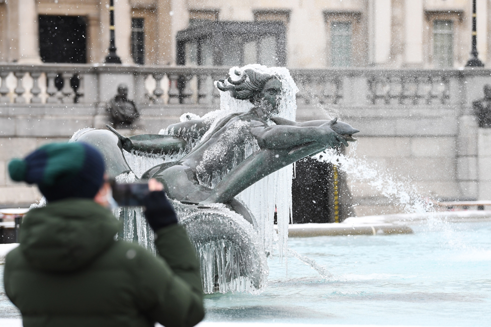 A man takes a photograph of an ice-covered mermaid statue in Trafalgar Square, London, on 9 February 2021