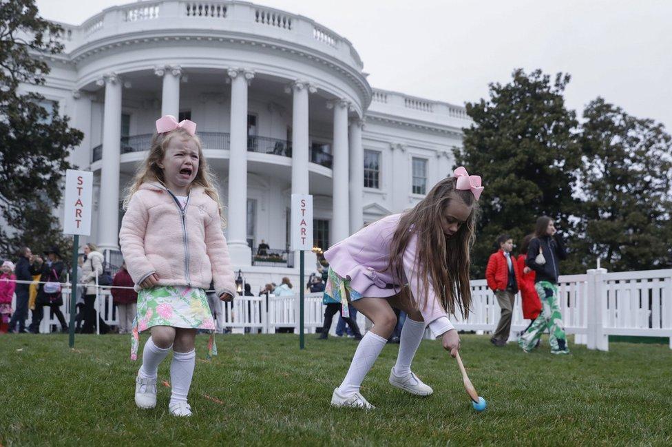 فيكتوريا إيويرز وشقيقتها إل تشاركان في الاحتفال بعيد القيامة في حديقة البيت الأبيض في العاصمة الأمريكية واشنطن. يستطيع الأطفال من جميع أنحاء الولايات المتحدة المشاركة في الاحتفال، الذي يستضيفه الرئيس دونالد ترامب، إذا فازوا بتذاكر عبر يانصيب على الإنترنت.
