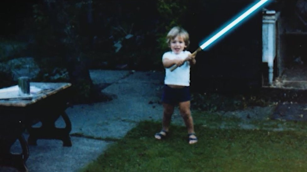 David Whiteley with 'lightsaber' in garden