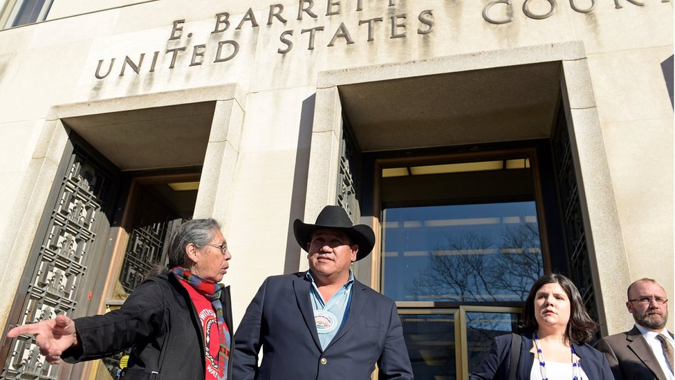 Cheyenne River Sioux Chairman Harold Frazier (C) talks to Madonna Thunder Hawk, left, of the Oohenumpa band of the Cheyenne River Sioux Tribe, before speaking to reporters outside federal court in Washington, Monday, Feb. 13, 2017