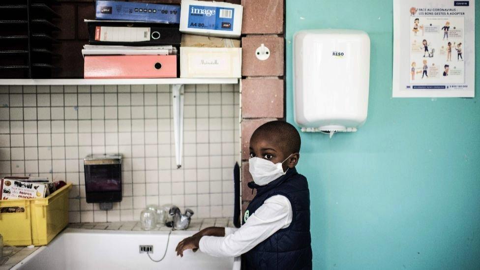 Menino lavando as mãos na escola na França, 14 May 2020