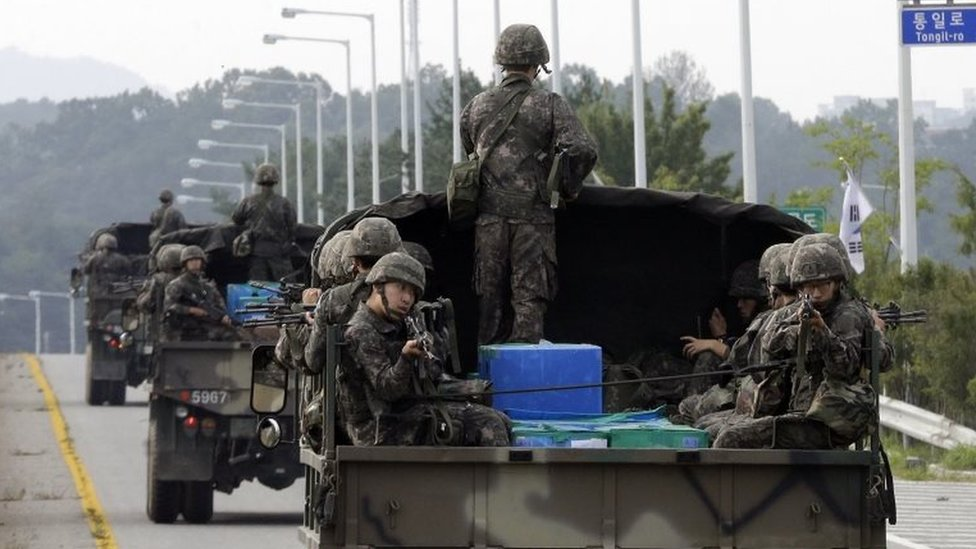 South Korean army soldiers ride on trucks in Paju, south of the demilitarized zone that divides the two Koreas, South Korea, Monday, Aug. 24, 2015.