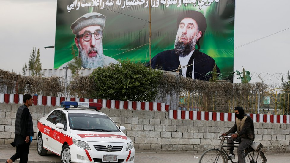 An Afghan man rides on his bicycle past a banner with pictures of Afghan warlord Gulbuddin Hekmatyar in Kabul, Afghanistan on 2 May 2017